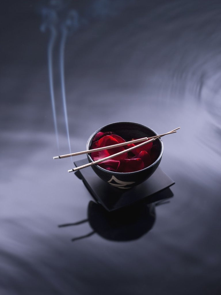 Detail of Burning incense on top of bowl of petals by Corbis