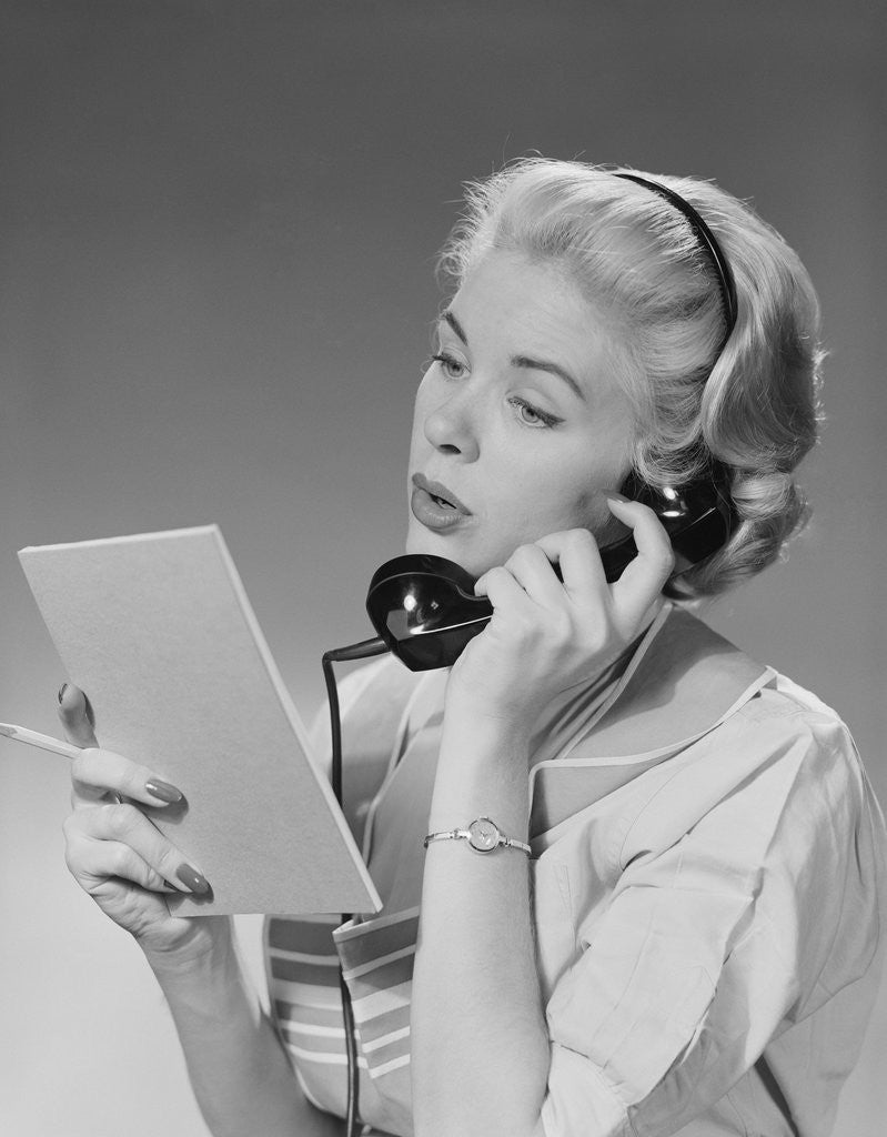 Detail of Blond woman talking on telephone reading list by Corbis