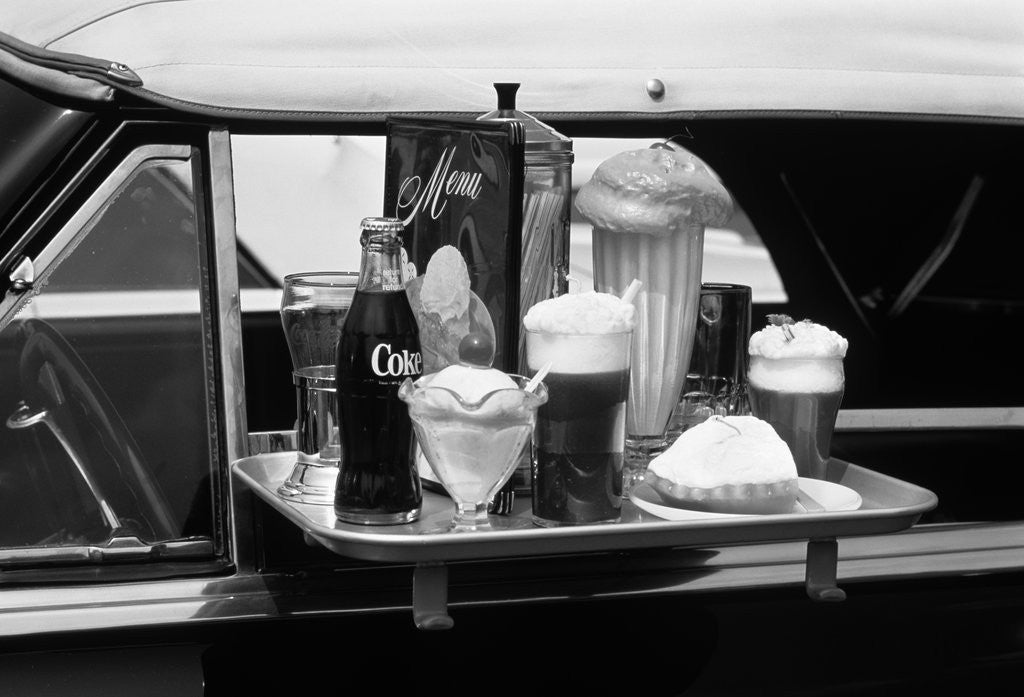 Detail of Food tray with soda fountain items on car window at 1950s style drive-in restaurant by Corbis