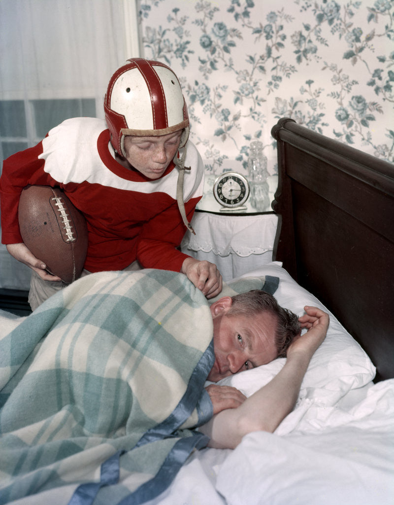 Detail of Boy in football uniform waking father asleep in bedroom by Corbis