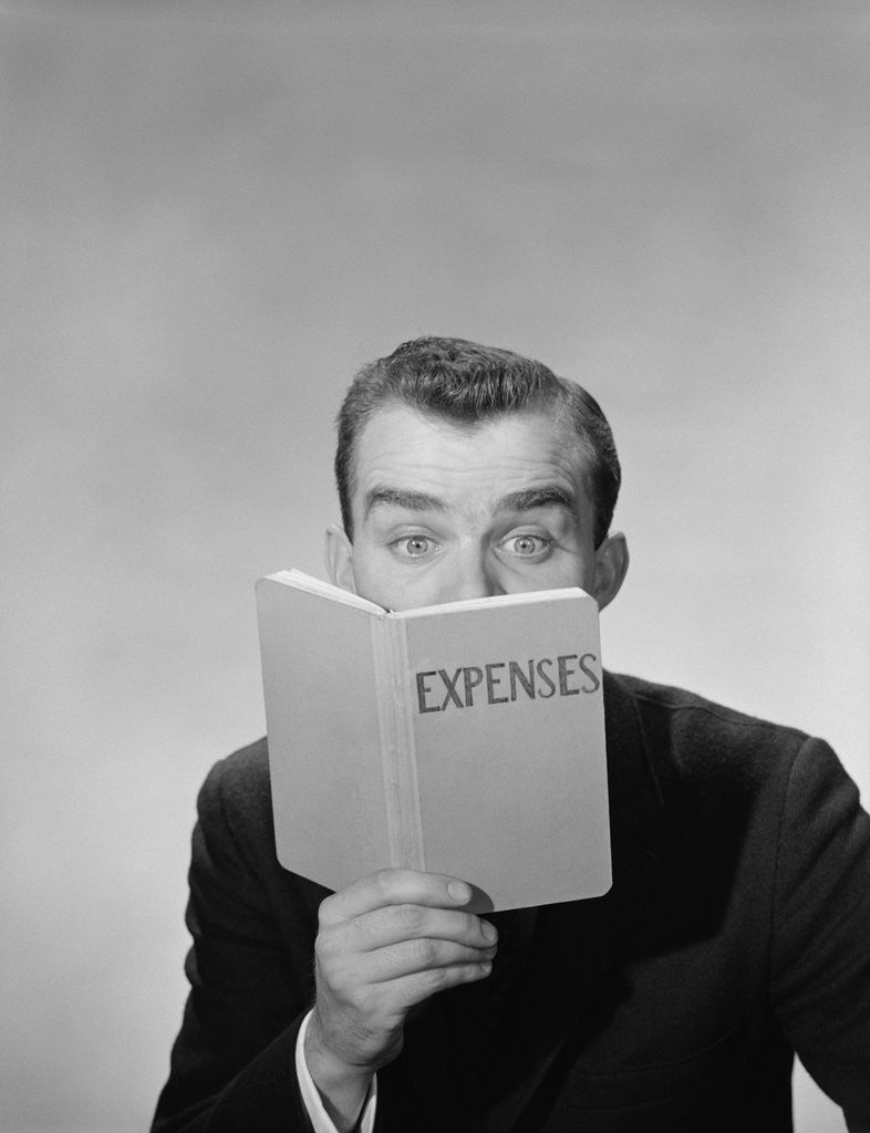 Detail of Man wide open eyes looking into expenses book hiding his lower face by Corbis