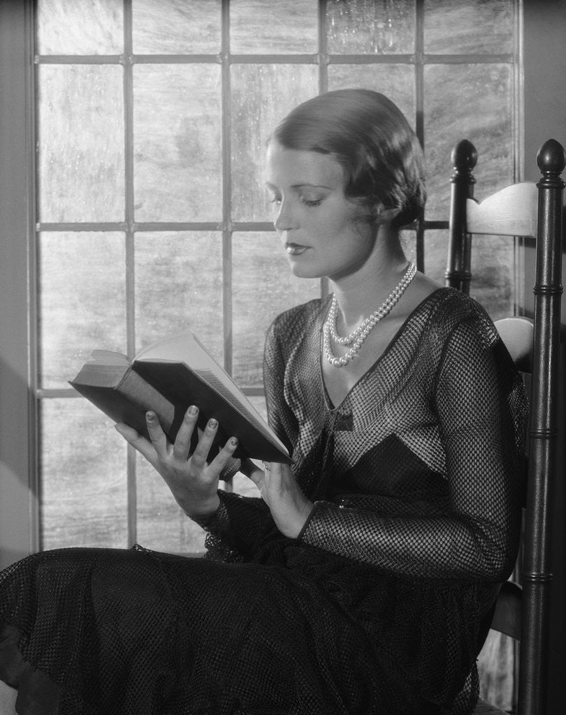 Detail of Elegant woman wearing pearls sitting by window reading book by Corbis