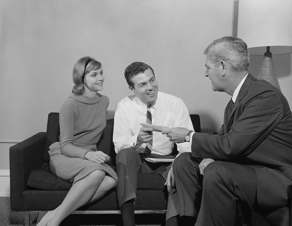 Detail of Couple sitting on couch talking to salesman by Corbis
