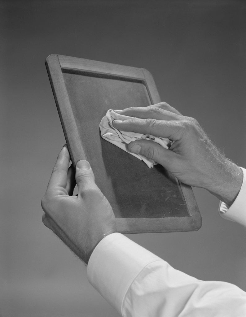 Detail of Male hands wiping slate clean by Corbis