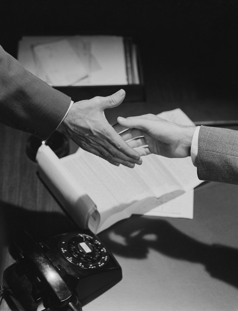 Detail of Close-up two male hands about to shake over desk with papers and telephone by Corbis