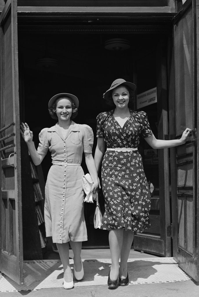 Detail of Two smiling women walking out doorway of a store by Corbis