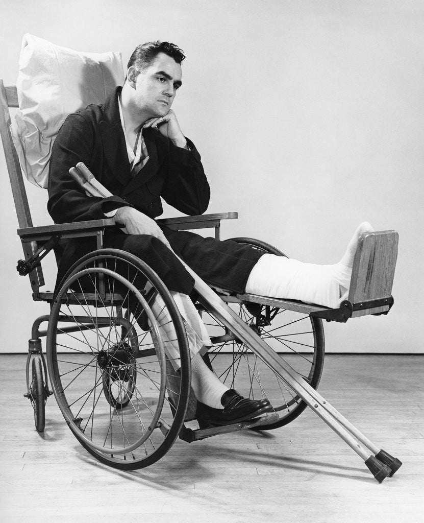 1940s man in wheelchair with cast on left leg holding crutches