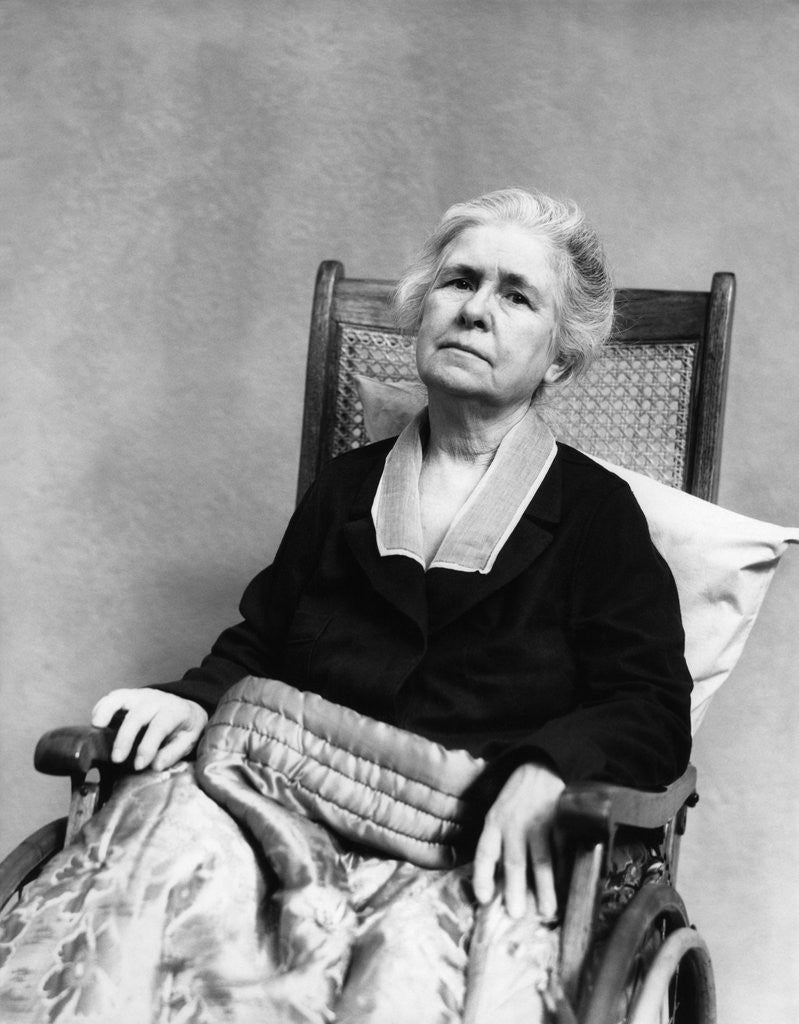 Detail Of 1930s Geriatric Sad Senior Old Woman In Wheelchair Looking At Camera Crippled By Age