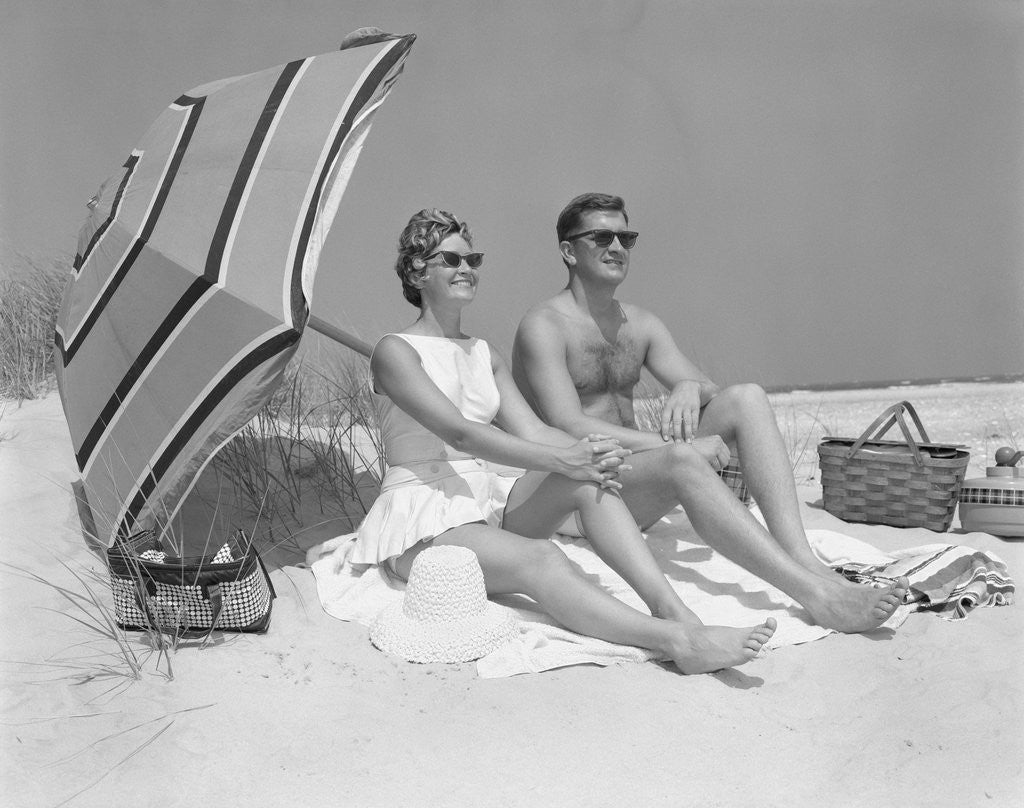 Detail of 1960s couple in sunglasses sitting on beach blanket with legs extended with umbrella by Corbis