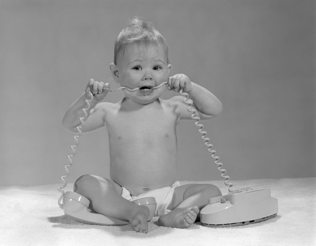 Detail of 1960s blond baby sitting up looking at camera chewing on telephone cord by Corbis