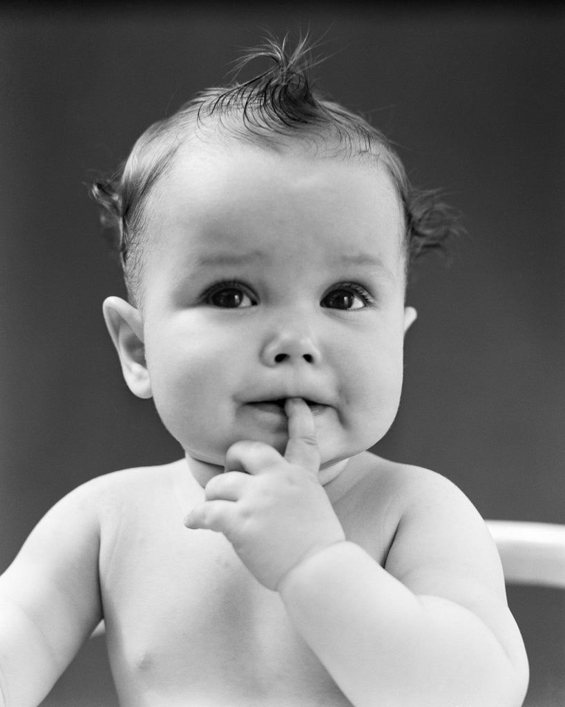 Detail of 1940s thoughtful baby with finger in mouth by Corbis