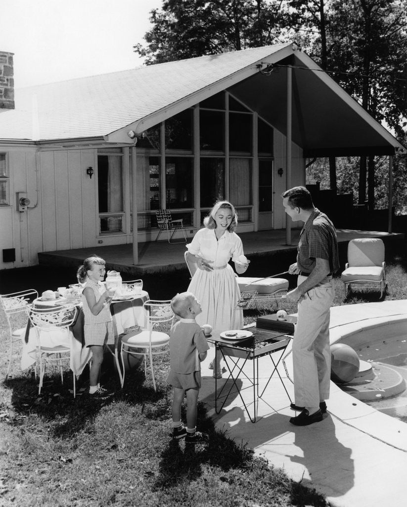 1950s family grilling hamburgers beside pool in backyard cookout by Corbis