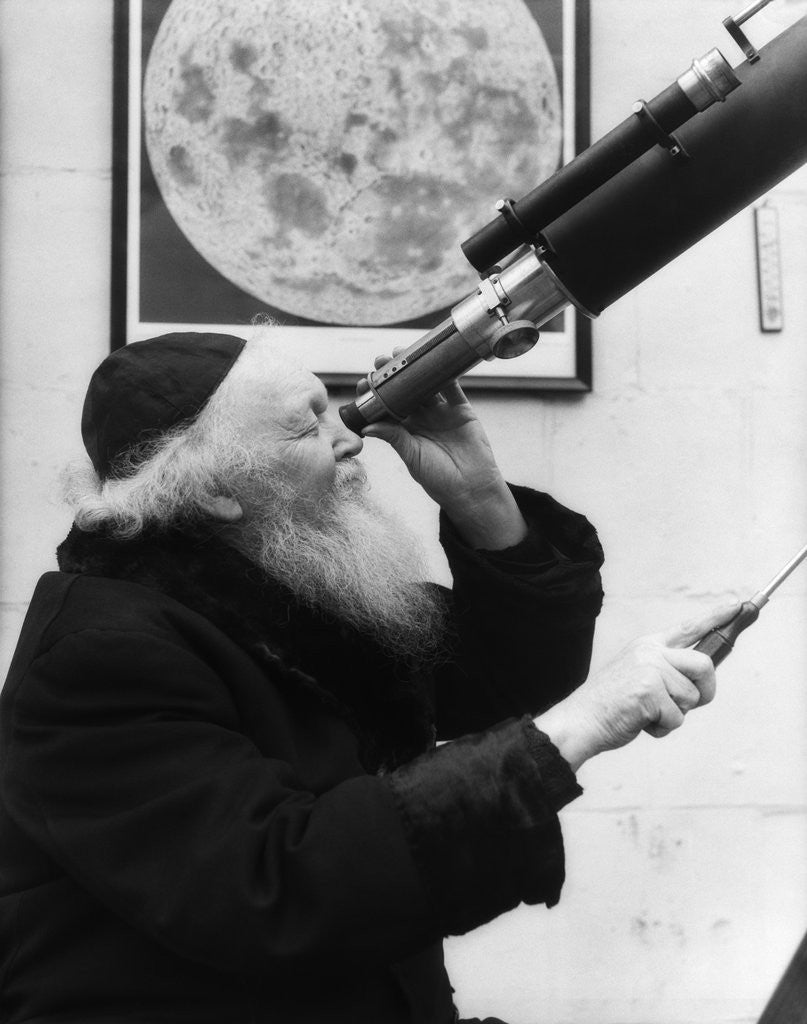 Detail of 1930s old astronomer white hair and beard wearing skull cap looking through telescope by Corbis