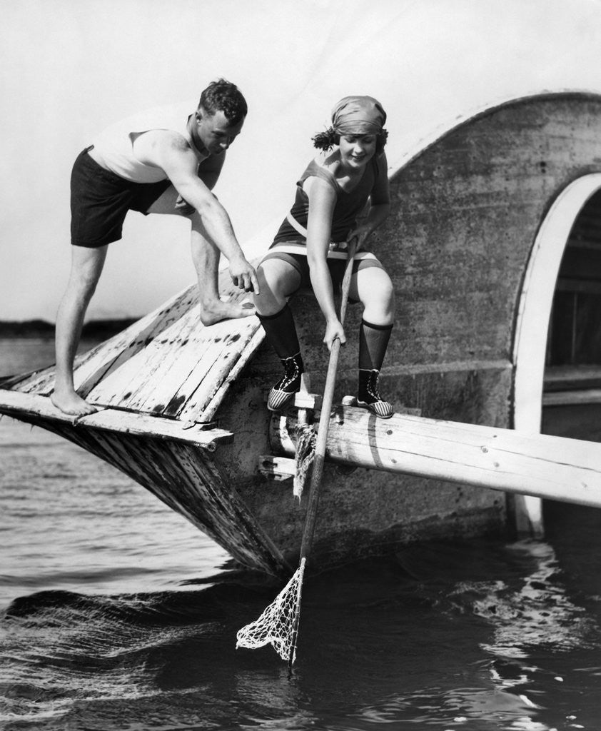 Detail of 1920s man and woman in bathing suits crabbing off old abandoned wooden boat by Corbis