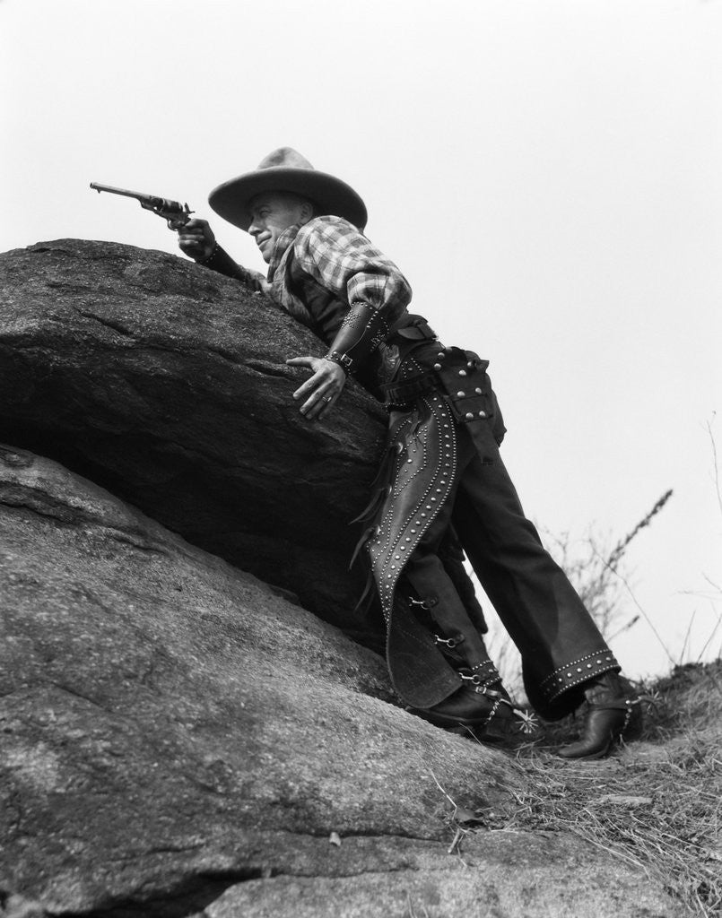 Detail of 1920s cowboy among rocks aiming revolver by Corbis