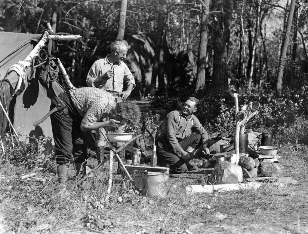 Detail of 1930s three men at campsite one washing his face at tripod wash stand the other tending campfire lake of the woods ontario canada by Corbis