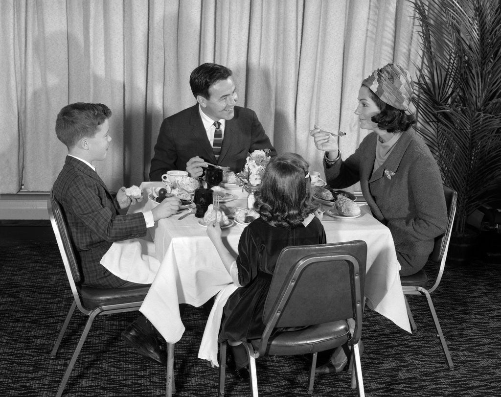 Detail of 1960s smiling happy family of four eating meal in restaurant dad talking to mom who is wearing turban style hat by Corbis
