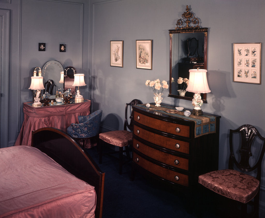 Detail of 1930s 1940s bedroom with blue walls pink bedspread and skirted vanity table by Corbis