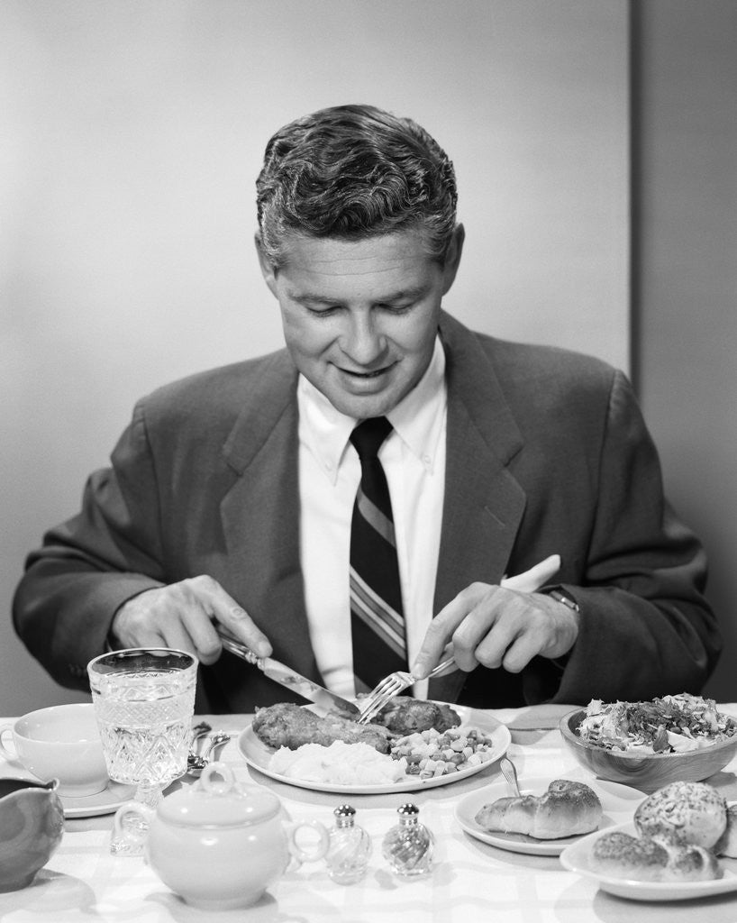 Detail of 1950s smiling man in suit and tie sitting at table holding knife and fork eating dinner by Corbis