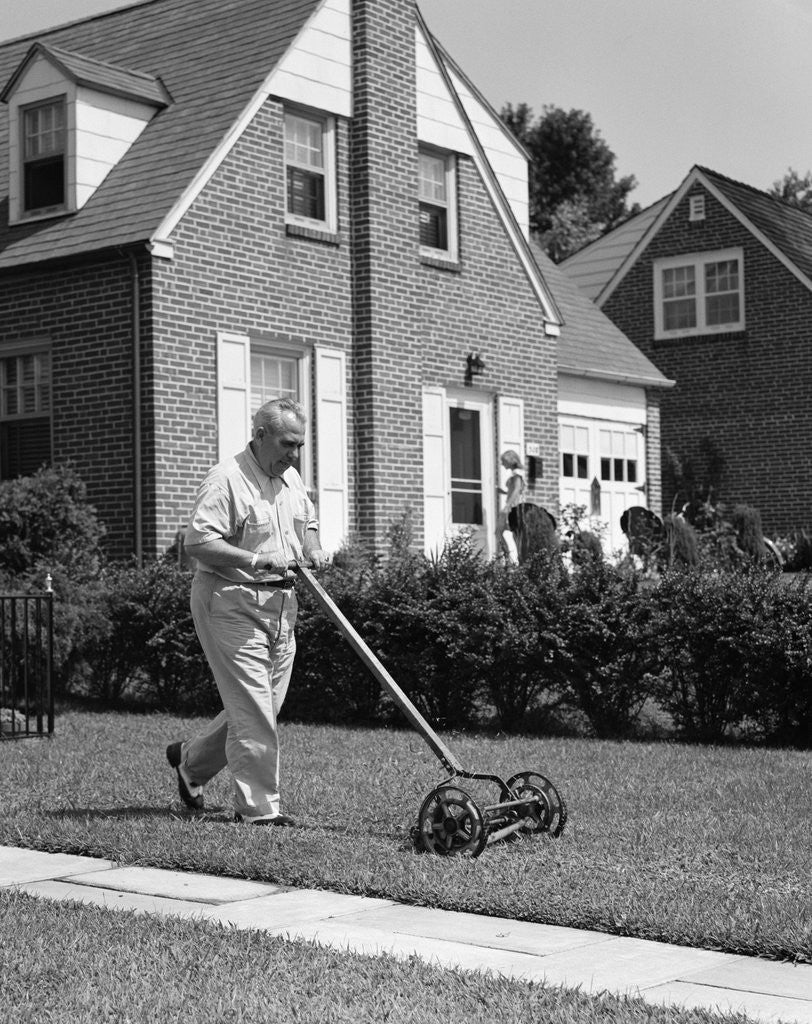 Detail of 1940s 1950s elderly overweight man pushing lawn mower in front of brick house by Corbis