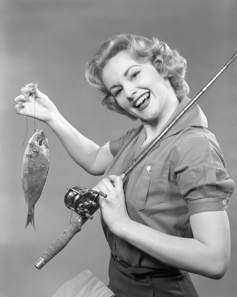 Detail of 1950s smiling woman with a fishing rod over her shoulder holding up a fish looking at camera by Corbis
