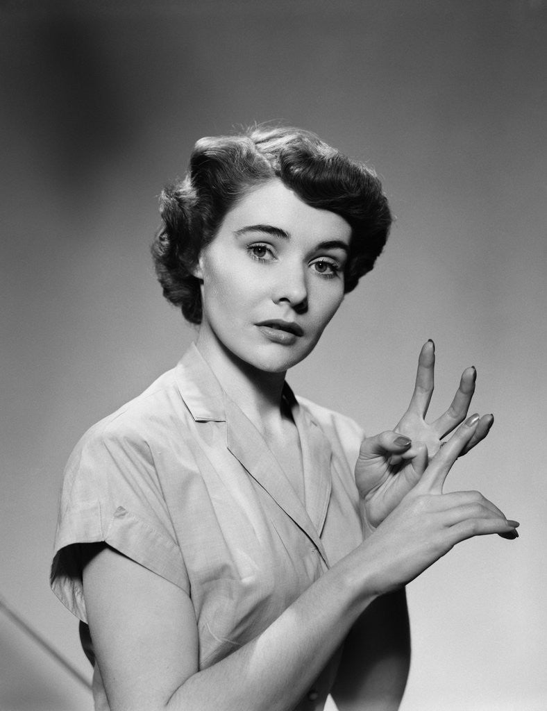 Detail of 1950s serious woman counting on hands by Corbis