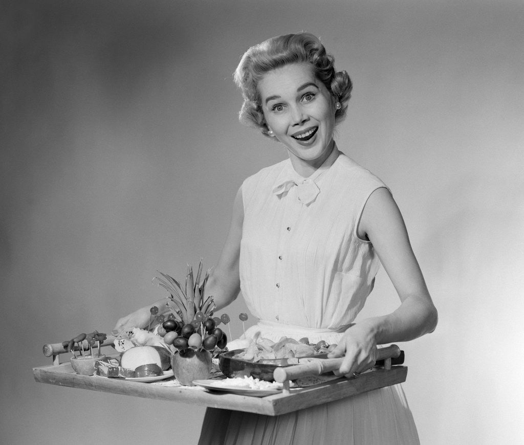 Detail of 1950s woman looking at camera smiling holding platter of hors d'oeuvres snacks by Corbis
