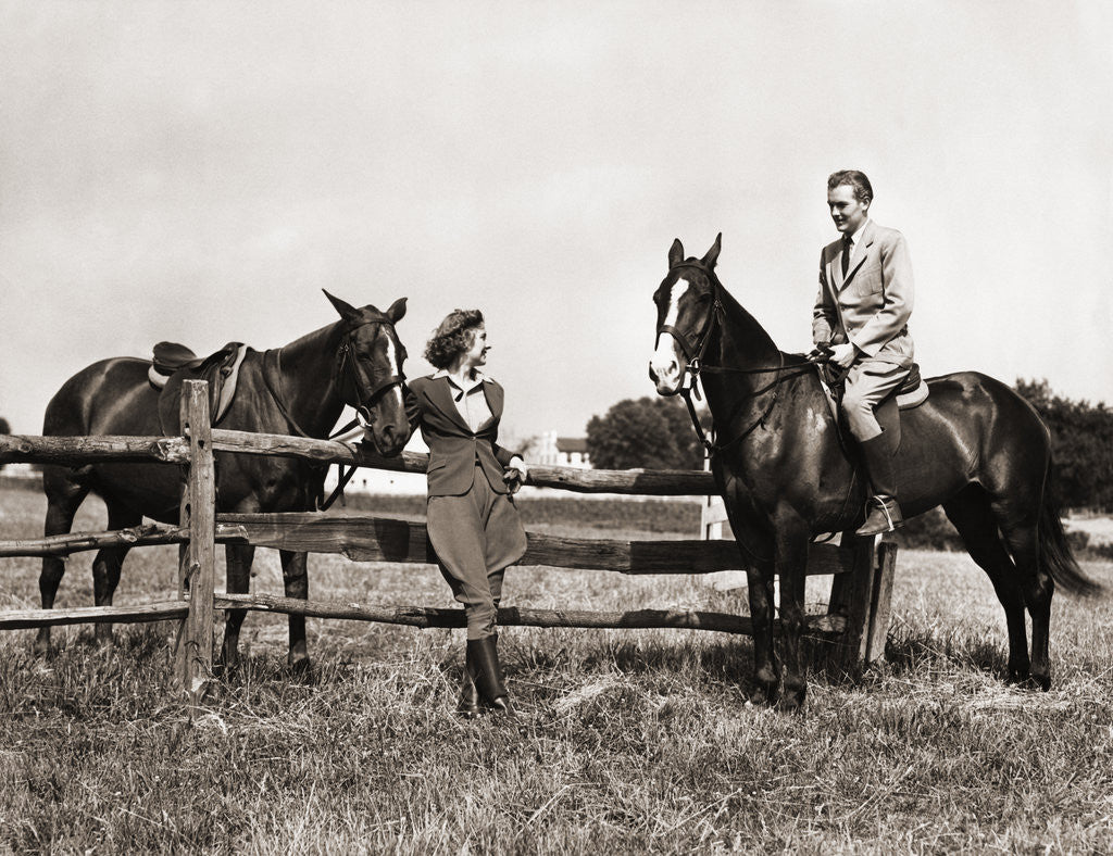 Detail of 1930s 1940s couple in riding gear man riding horse woman standing by wooden fence by Corbis