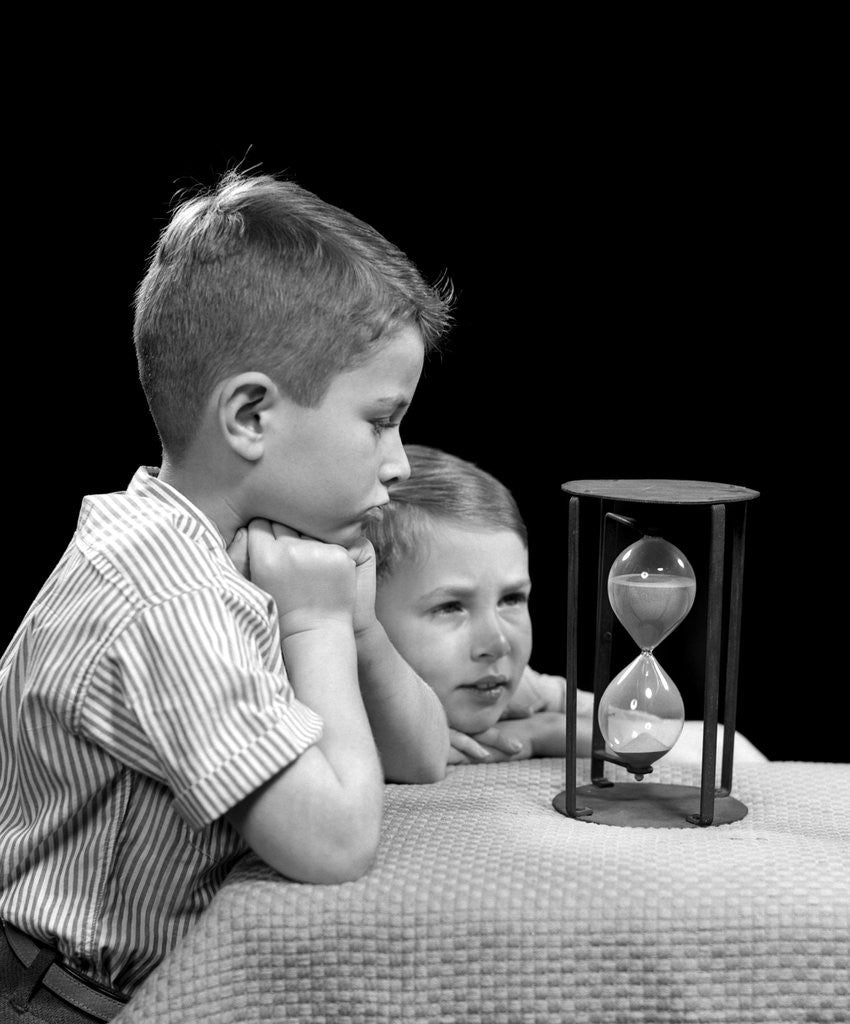 Detail of 1940s two boys waiting watching sand falling in hourglass by Corbis