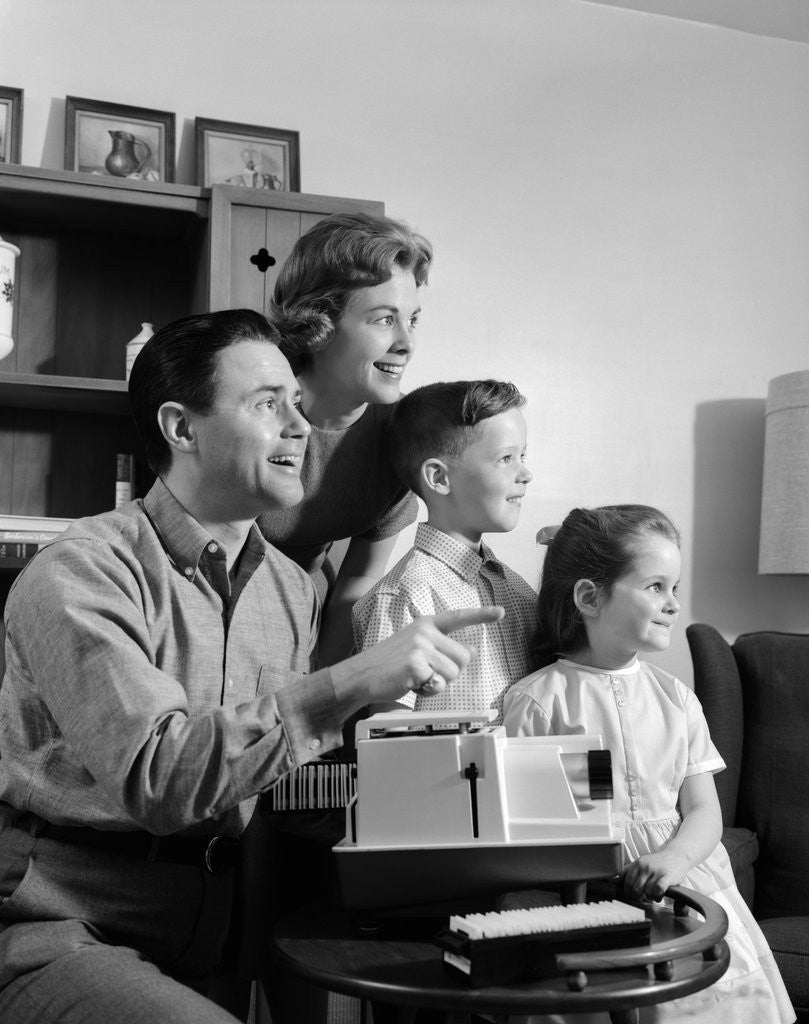 Detail of 1960s happy family looking at slides on slide projector by Corbis