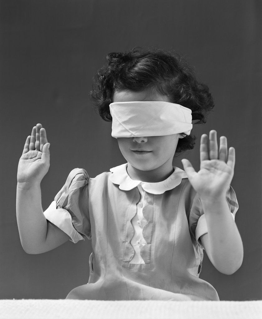 Detail of 1940s child wearing blind fold with hands up in the air by Corbis