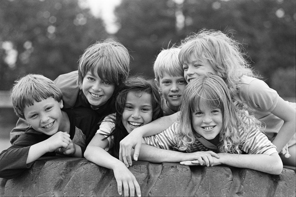 Detail of 1970s 1980s group of six boys & girls gathered together on large playground tire by Corbis