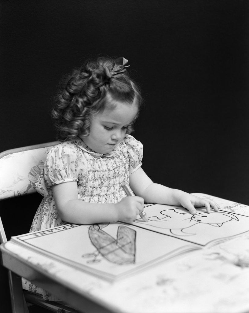 Detail of 1960s 1940s girl child sitting at desk drawing coloring pictures by Corbis