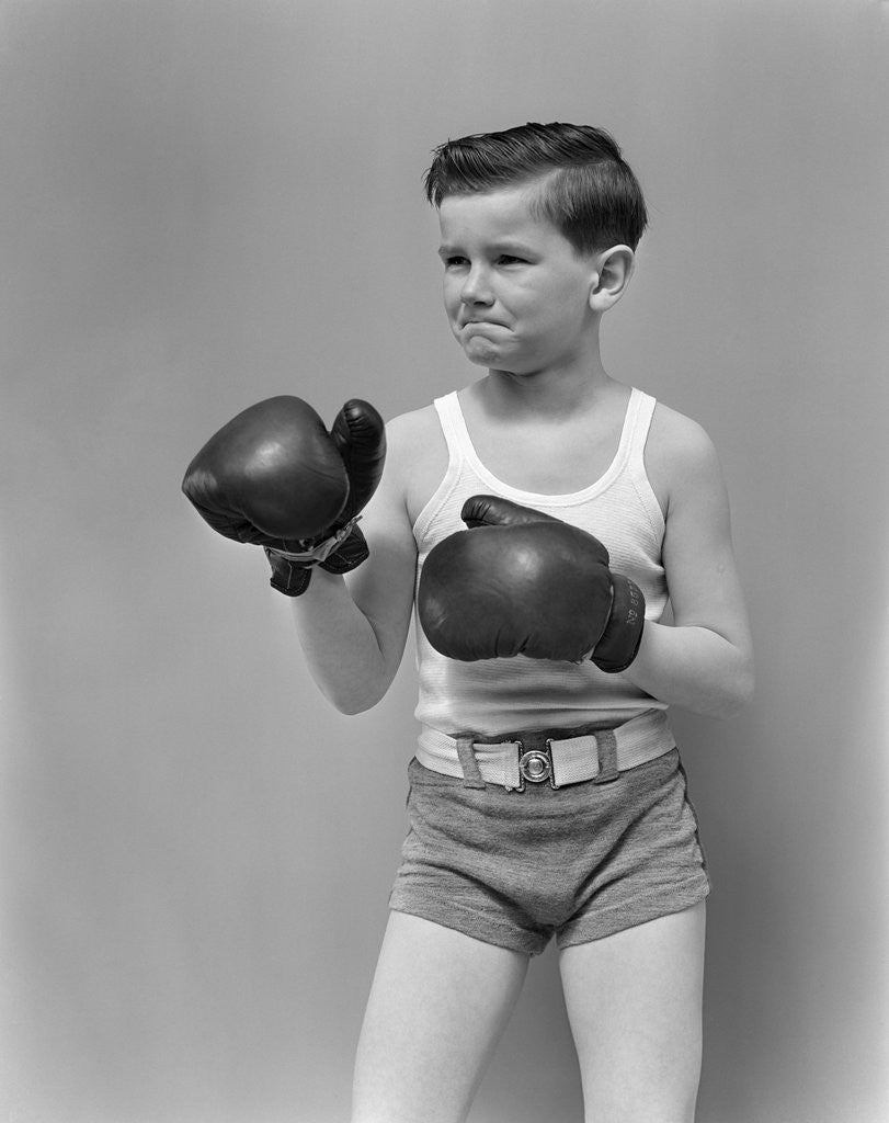 Detail of 1940s boy child wearing boxing gloves standing ready to fight by Corbis