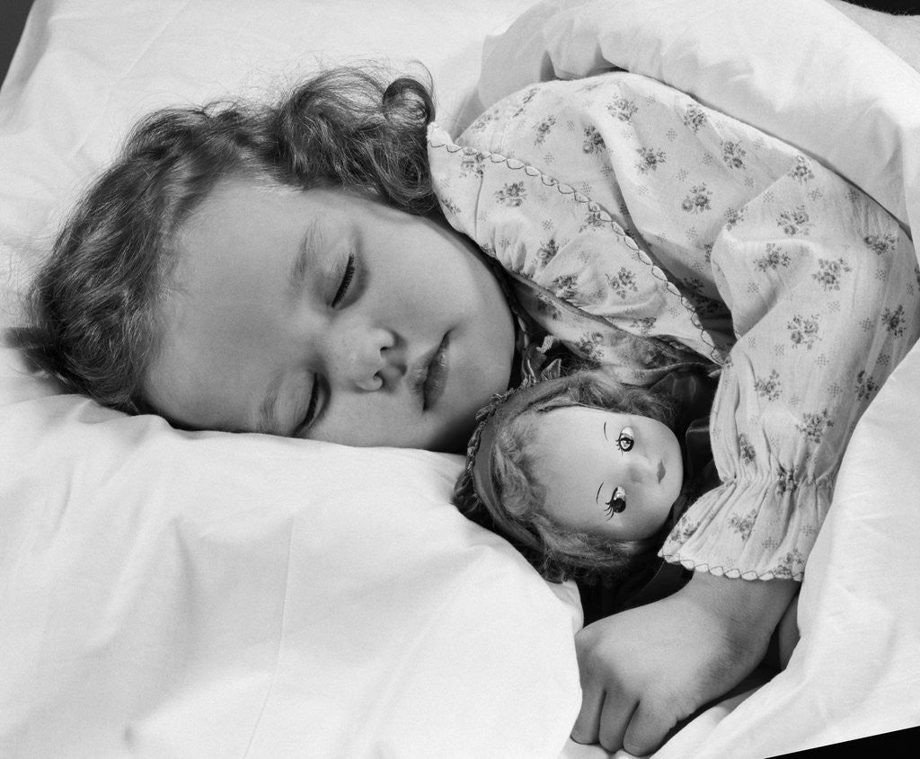 Detail of 1950s child little girl sleeping in bed with doll by Corbis