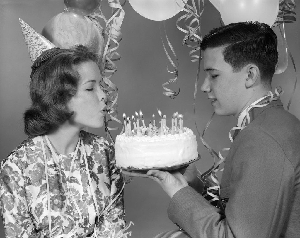 1960s Teenage Girl Blowing Out Candles On Birthday Cake Held By Boy