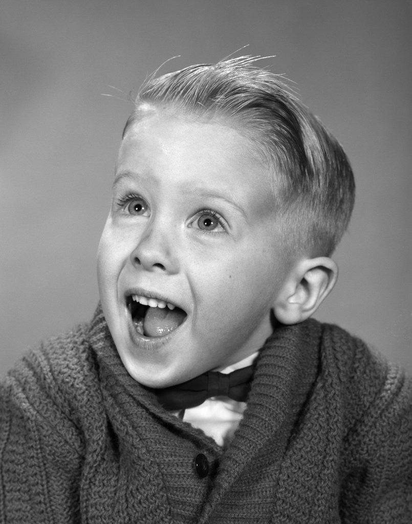 Detail of 1960s young blond boy with happy surprised facial expression by Corbis