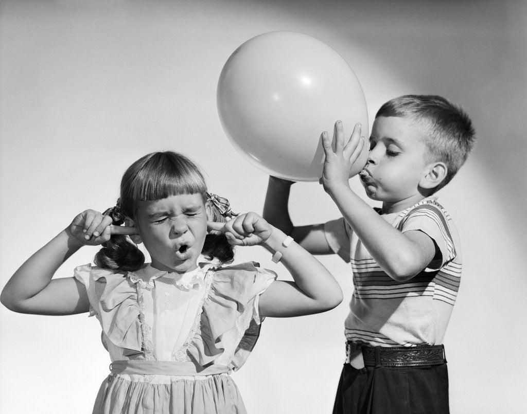 Detail of 1950s little boy blowing up big balloon little girl with fingers in ears eyes closed by Corbis