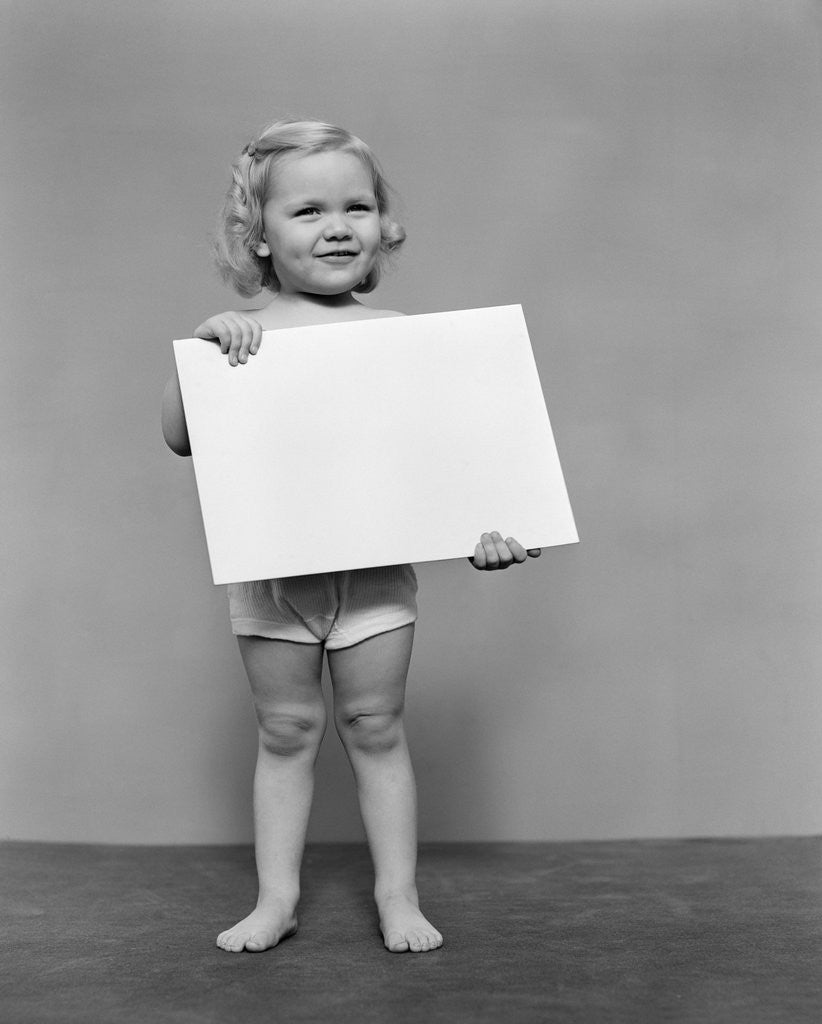 Detail of 1940s blond toddler girl holding blank card sign by Corbis