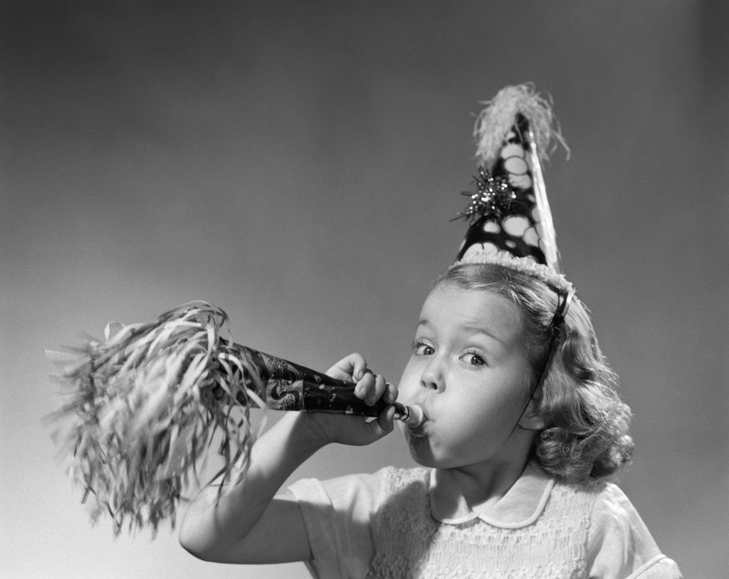 Detail of 1950s girl wearing party hat blowing into noise maker looking at camera by Corbis