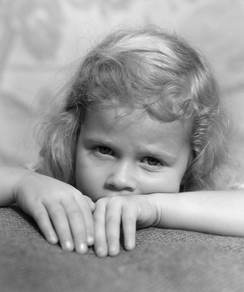Detail of 1930s portrait sad little blond girl peeking over her hands looking at camera by Corbis