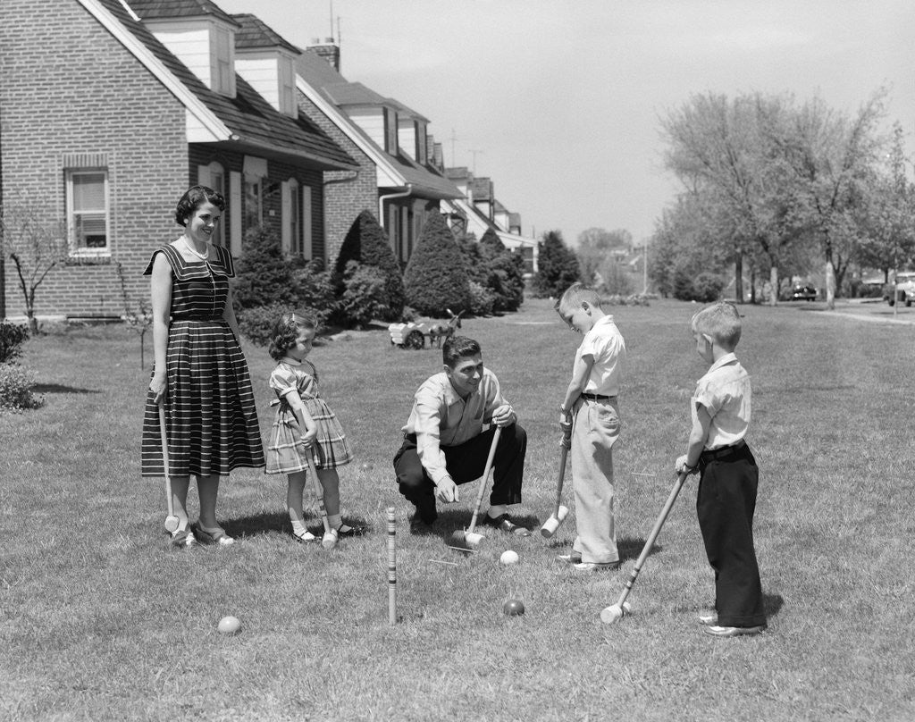 Detail of 1950s family mother father 3 children playing croquet front lawn suburban home by Corbis