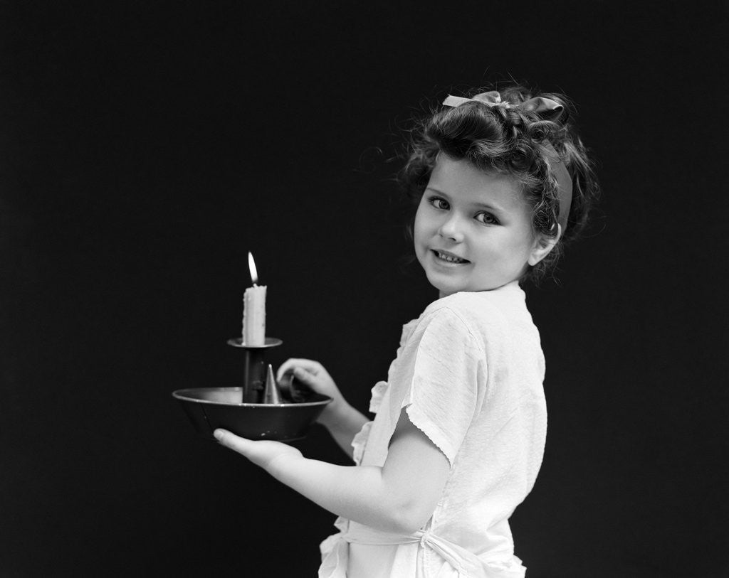 Detail of 1940s child little girl holding candle looking at camera by Corbis