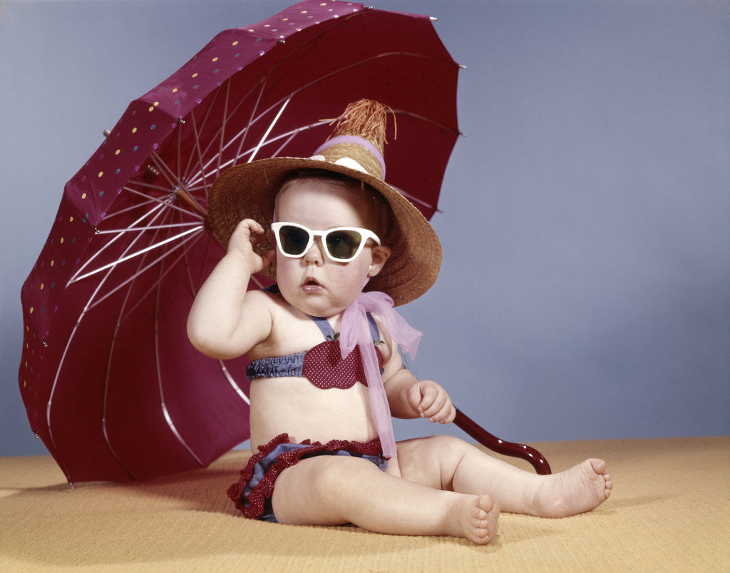 Detail of 1960s baby girl wearing two piece bikini and straw hat sunglasses sitting by red beach umbrella by Corbis