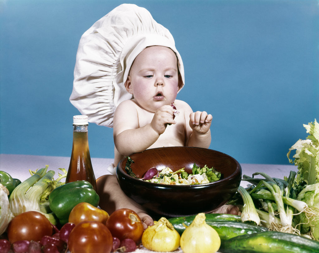 4f349a41f 1960s baby making salad wearing chef hat with variety of fresh ingredients  vegetables