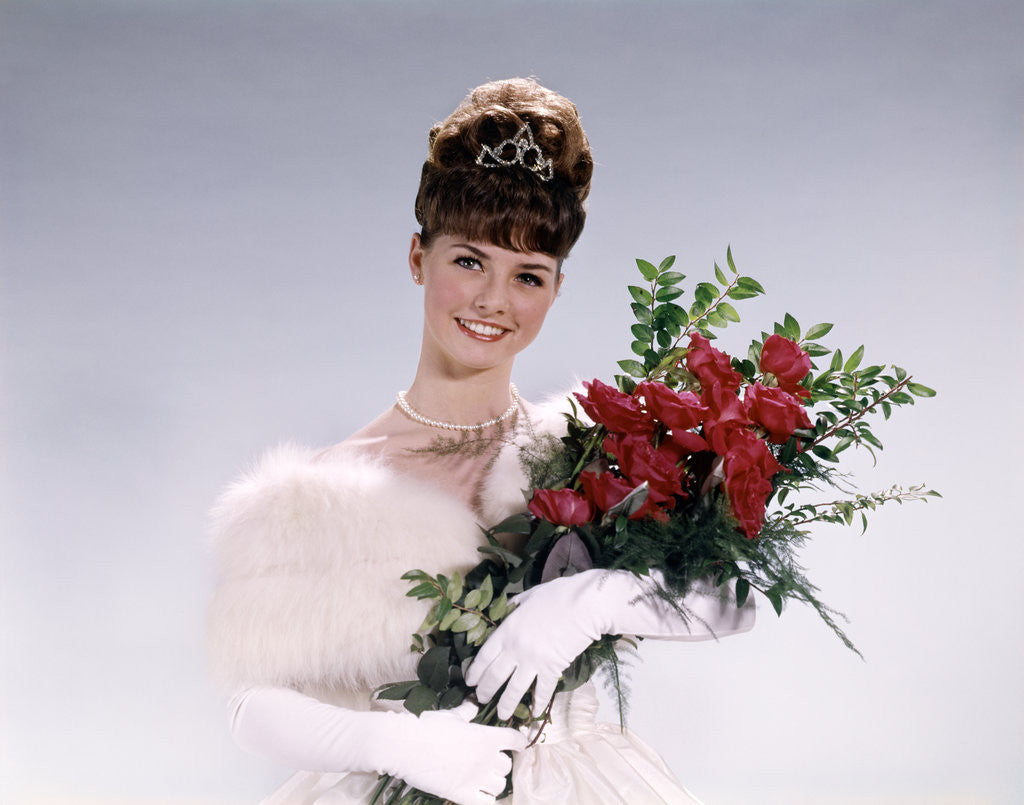 Detail of 1960s woman prom queen wearing white evening dress holding bouquet of flowers red roses looking at camera by Corbis