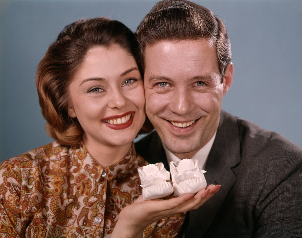 Detail of 1960s smiling couple holding baby shoes looking at camera by Corbis