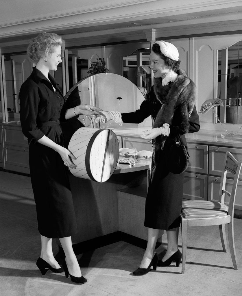 Detail of 1950s woman in hat stole & gloves taking hatbox from saleswoman by Corbis