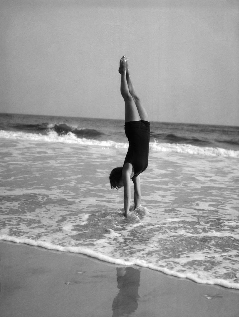 1920s woman doing a handstand in ocean surf by Corbis