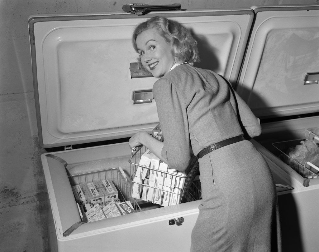 Detail of 1950s blond woman lifting wire basket food items from a deep freezer looking at camera over her shoulder by Corbis